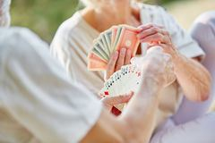 two-retired-seniors-playing-cards-as-hobby-garden-summer-92904869
